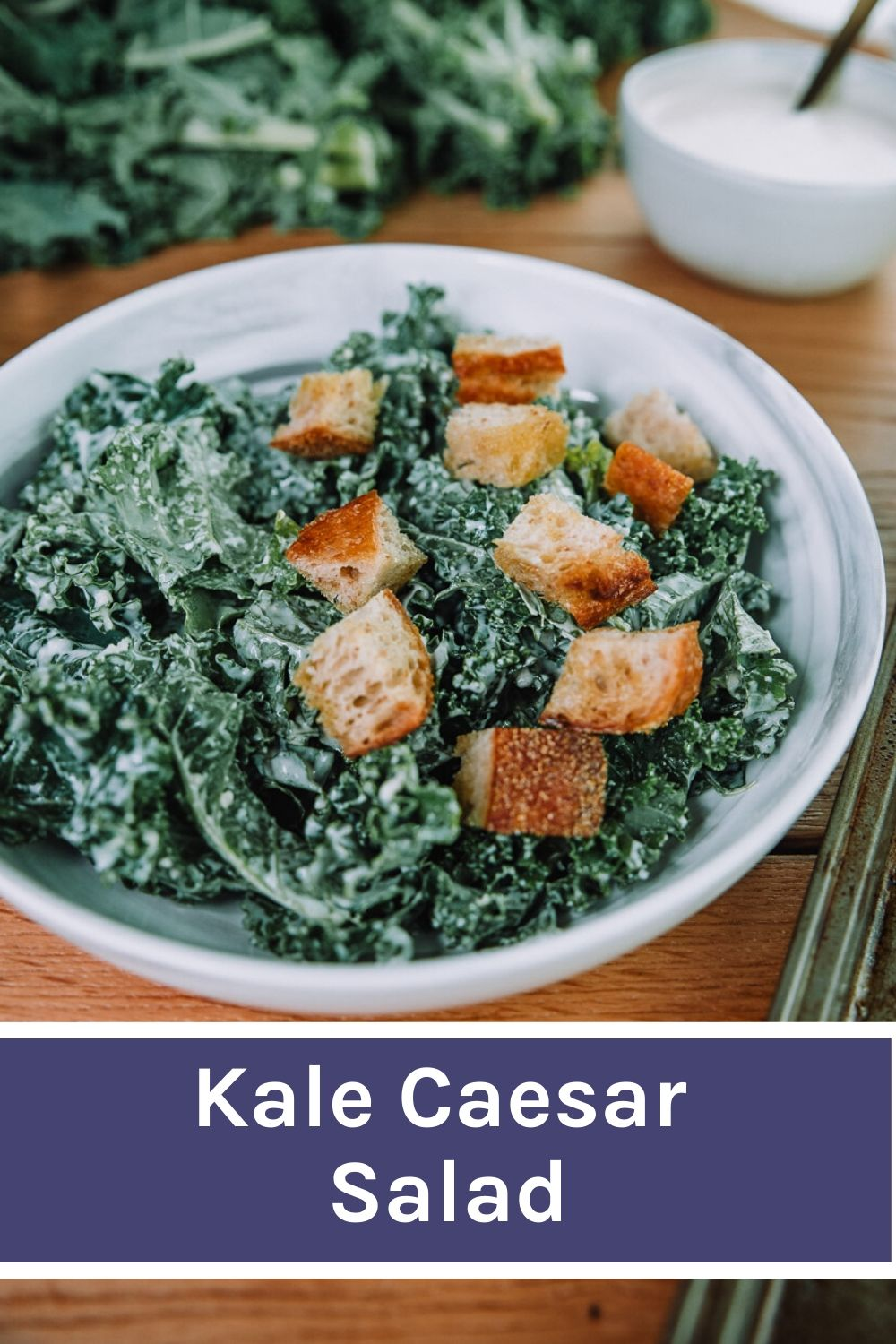 Kale Caesar Salad with fresh baked croutons in a white bowls on a wood table . Kale Caesar salad recipe by Farmer's Market Society.  Market Inspired Meals. #foodphotography #recipe #caesarsalad Easy salad ideas, Caesar salad dressing, green salad, fresh salad, lunch ideas, simple salads, croutons, quick salad ideas, make ahead meals.