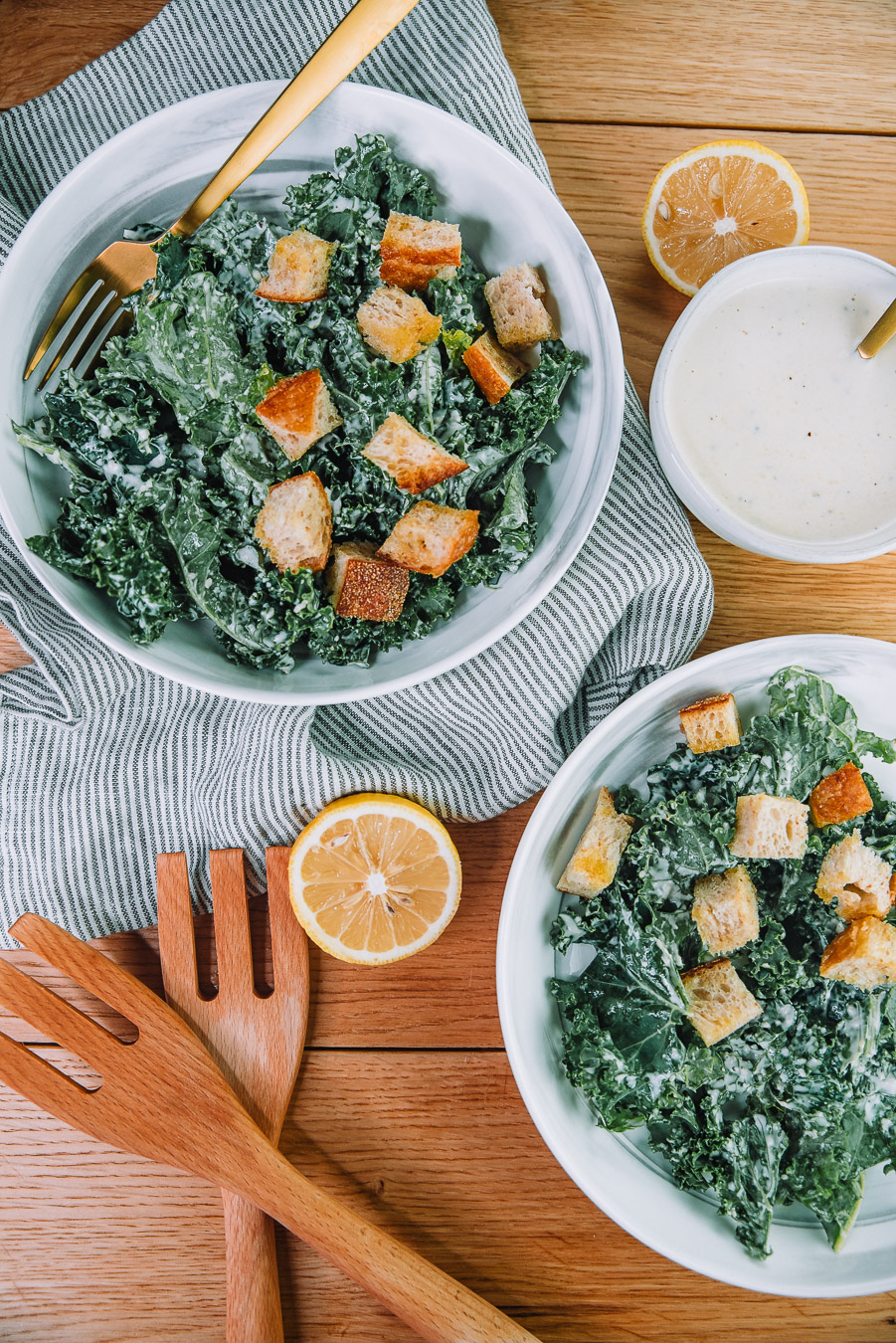 Kale Caesar Salad with fresh baked croutons in 2 white bowls on a wood table with 2 salad tongs, lemons, and a kitchen towel. Kale Caesar salad recipe by Farmer's Market Society.  Market Inspired Meals.