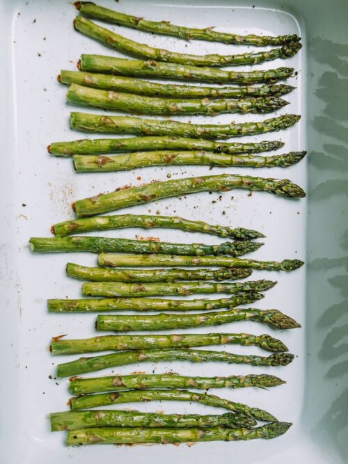 Roasted asparagus in a white baking dish