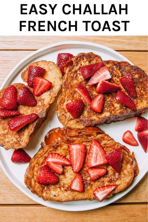 Thick luscious slices of French toast made with challah bread from the farmers market for easy homemade brunch topped with fresh strawberries. #brunch #frenchtoast #farmersmarket #strawberries