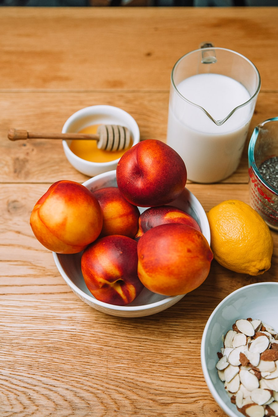 Milk, honey, lemon, almonds, chia seeds, and yellow nectarines in a bowl sitting on a wooden table
