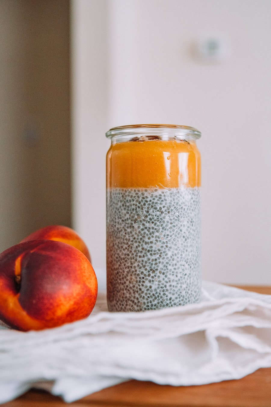 Jar of chia pudding with nectarines, a white table cloth, and wooden table.
