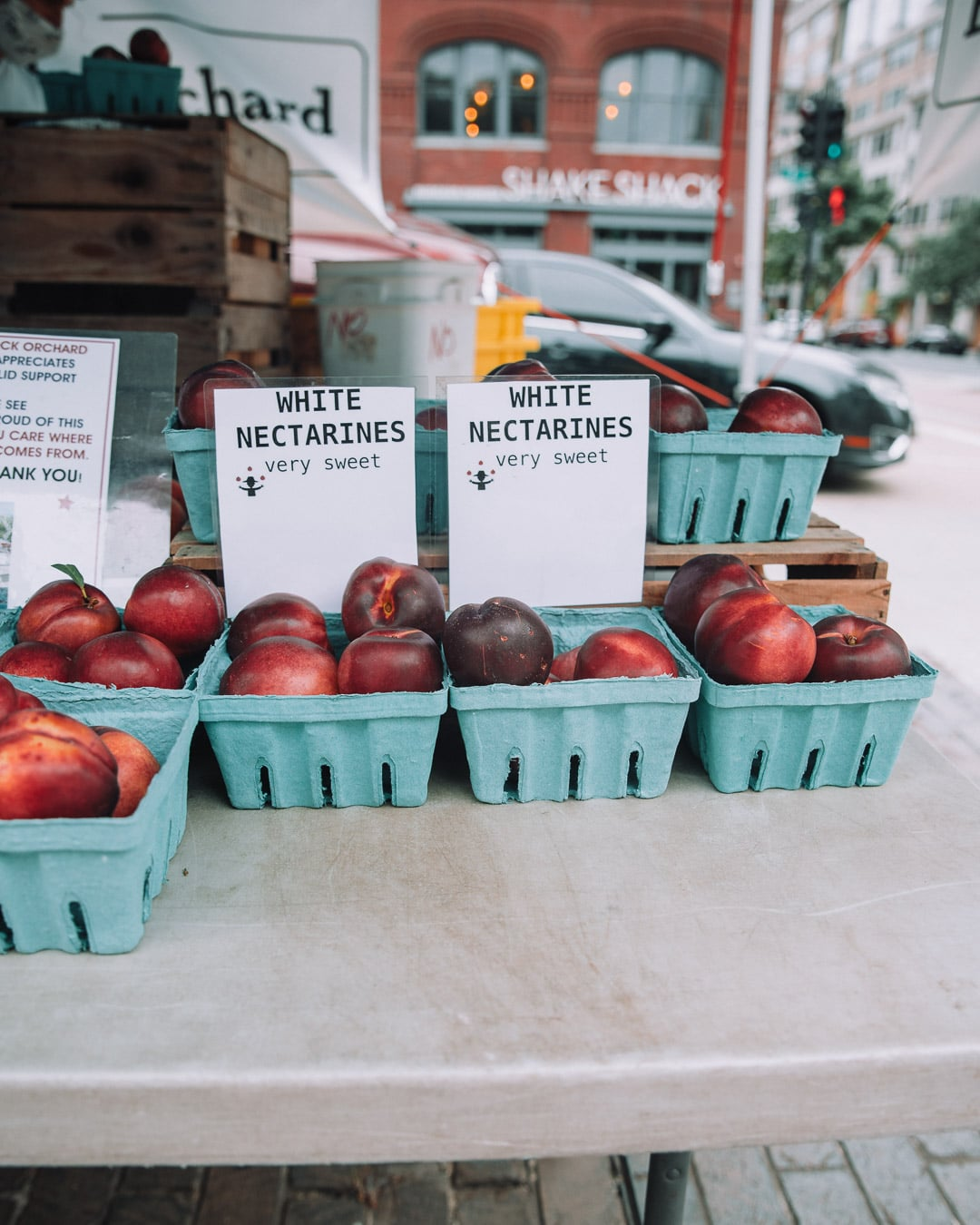 White nectarines in a cartons on a table at the farmers market.