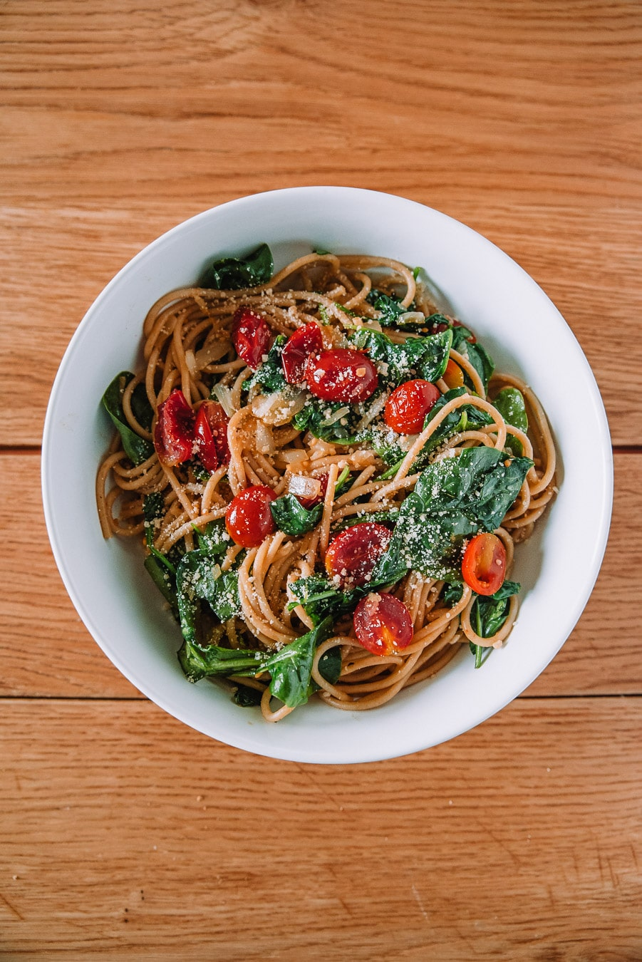 White bowl with pasta and roasted cherry tomatoes and spinach.